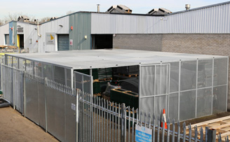 Large outdoor security cage for warehouse stock overflow.